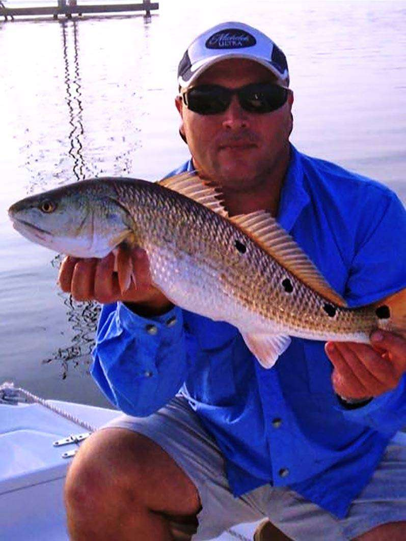 The fishing guide holding up a fresh caught redfish