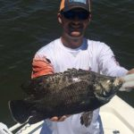 A fisherman with a fresh caught tripletail